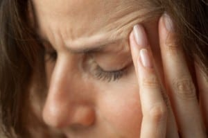 Woman suffering from a TMJ headache