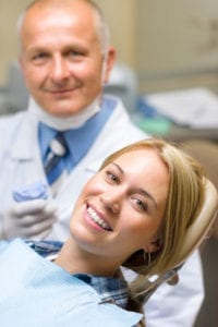 image of woman dental patient smiling in exam room with dentist in background