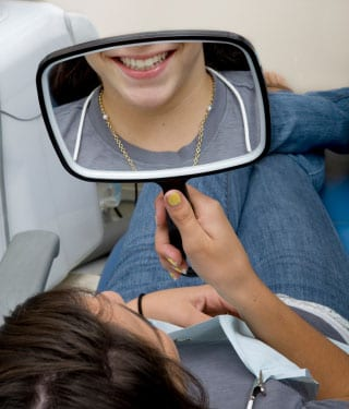 woman looking into a handheld mirror and smiling