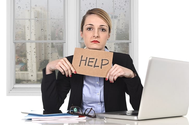 woman looking sad holding a help sign