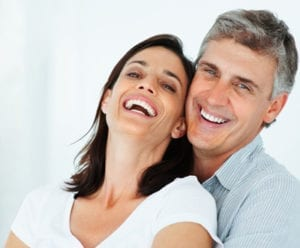 man and women smiling with man's arms around her from behind